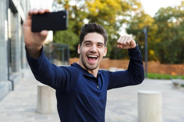 Souriant jeune sportif prenant un selfie assis à l'extérieur, posant