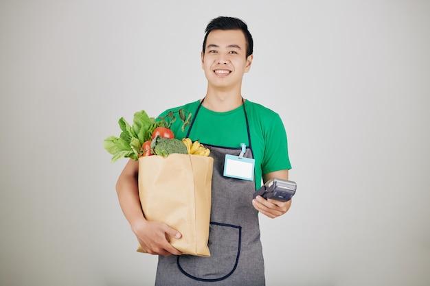 Souriant jeune travailleur de supermarché