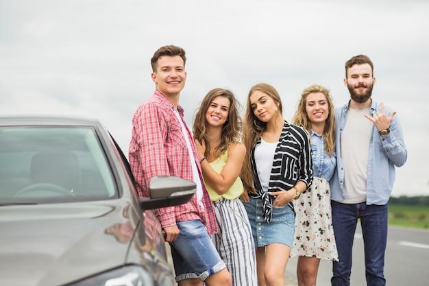 Souriant jeunes amis debout près de la voiture garée