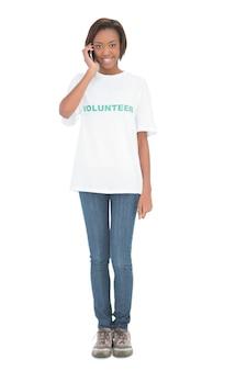 Souriant joli volontaire ayant un appel téléphonique