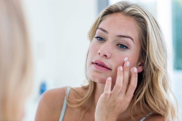 Souriant jolie femme appliquant la crème sur son visage dans la salle de bain
