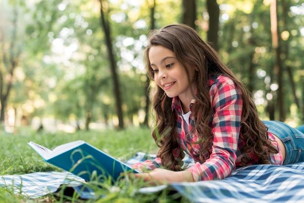 Souriant jolie fille lisant un livre en position couchée sur une couverture à carreaux au parc