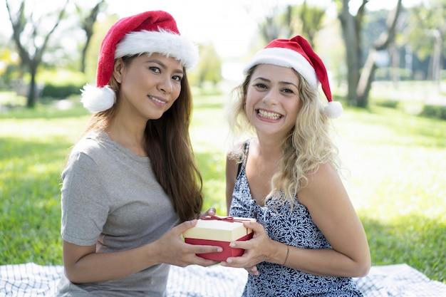Souriant de jolies femmes portant des chapeaux de père noël et tenant une boîte-cadeau