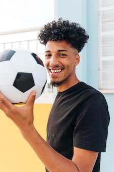 Souriant joueur de football tient le ballon et regarde la caméra