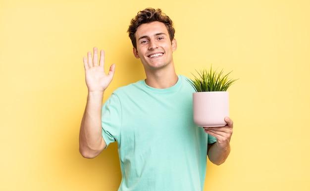 Souriant joyeusement et joyeusement, agitant la main, vous accueillant et vous saluant, ou vous disant au revoir. concept de plante décorative