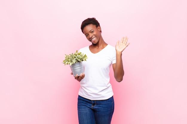 Souriant joyeusement et joyeusement, agitant la main, vous accueillant et vous saluant, ou vous disant au revoir