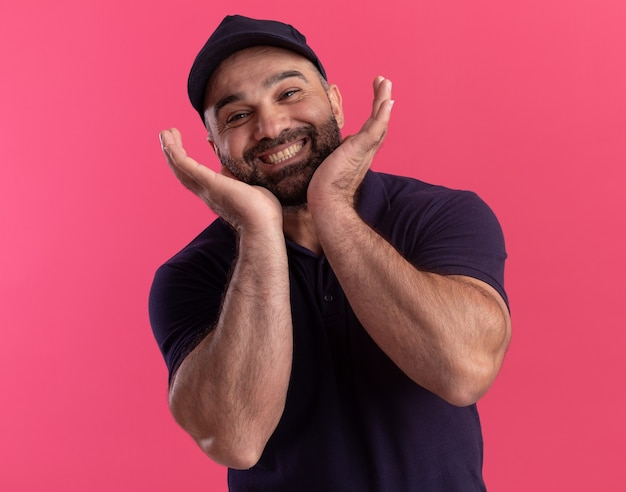 Souriant livreur d'âge moyen en uniforme et cap tenant autour du visage isolé sur mur rose