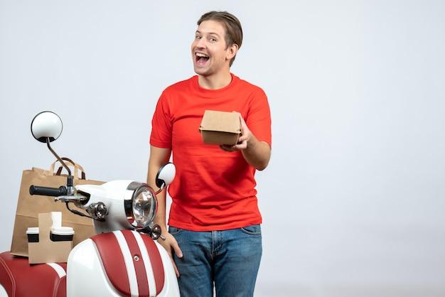 Souriant livreur en uniforme rouge debout près de scooter tenant une petite boîte sur fond blanc