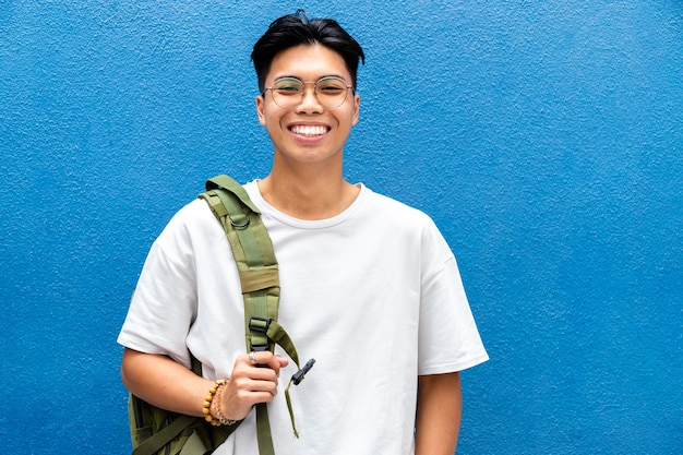 Souriant lycéen asiatique regardant la caméra avec sac à dos sur fond bleu espace de copie