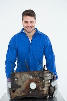 Souriant machanic mâle transportant le vieux moteur de voiture