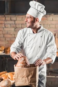 Souriant mâle boulanger mettant le pain dans un sac en papier brun