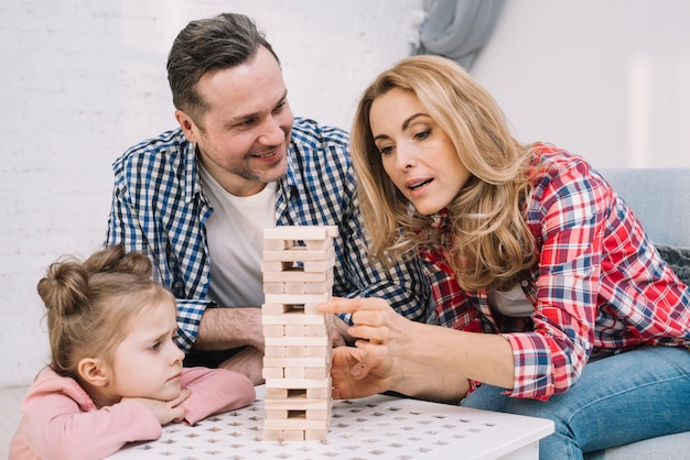 Souriant mari à la recherche de leur femme tout en organisant une tour de jeu en bloc