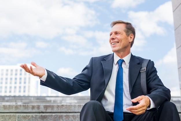 Souriant mature homme d'affaires assis sur l'escalier faisant le geste de la main