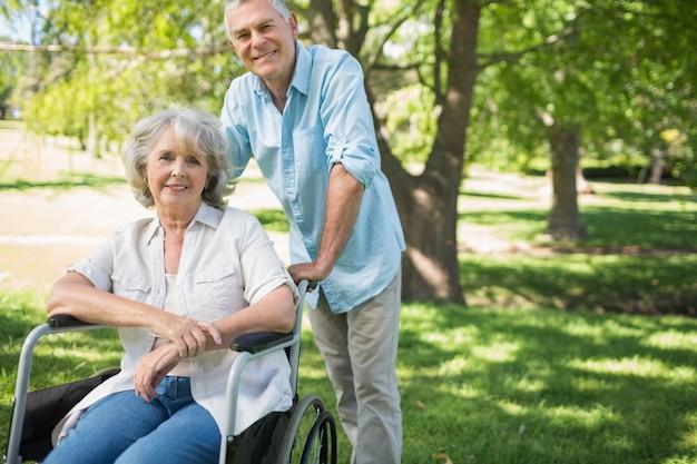 Souriant mature homme avec une femme assise dans une chaise roulante au parc