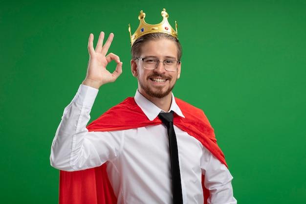 Souriant mec jeune super-héros portant couronne montrant le geste correct isolé sur vert
