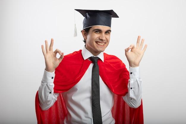 Souriant Mec Jeune Super-héros Portant Cravate Et Chapeau Diplômé Montrant Le Geste Correct Isolé Sur Fond Blanc Photo gratuit