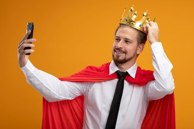 Souriant mec jeune super-héros portant cravate et couronne mettant la main sur la couronne et prendre un selfie isolé sur fond orange