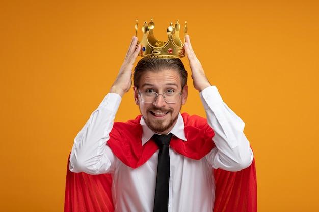 Souriant mec jeune super-héros portant une cravate et des lunettes mettant la couronne sur la tête isolé sur orange