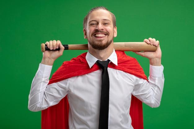 Souriant mec jeune super-héros portant une cravate mettant la batte de baseball sur le cou isolé sur vert