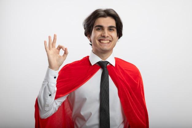 Souriant mec jeune super-héros regardant la caméra portant une cravate montrant un geste correct isolé sur fond blanc