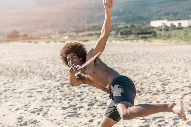 Souriant mec noir jouant au tennis de plage