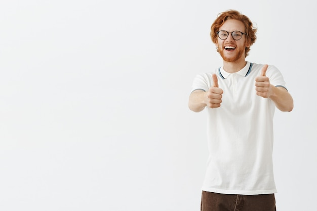 Souriant mec rousse barbu posant contre le mur blanc avec des lunettes