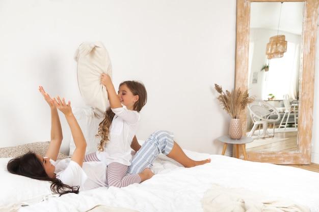 Souriant mère et fille jouant et s'amusant au lit tôt le matin
