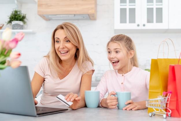 Souriant mère et fille à la recherche sur un ordinateur portable