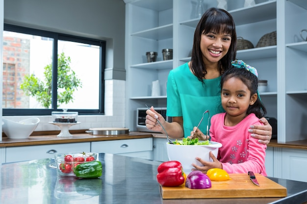 Souriant mère lavant la salade avec sa fille