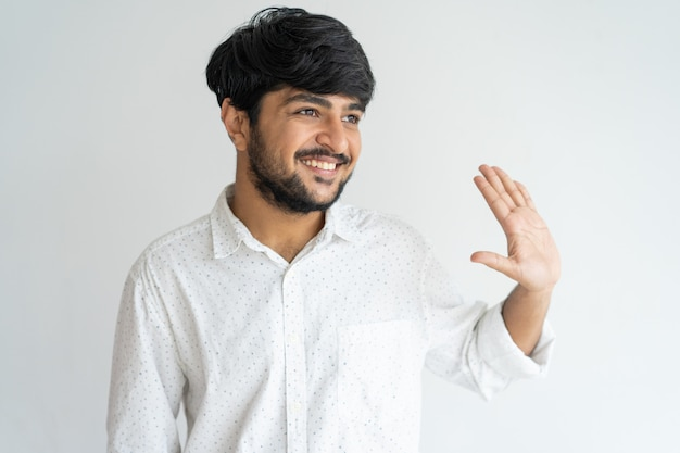 Souriant modeste jeune homme indien avec des cheveux épais agitant la main de côté.