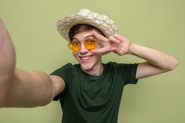 Souriant montrant un geste de paix jeune beau mec portant un chapeau avec des lunettes isolé sur un mur vert olive