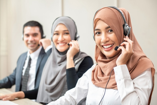 Souriant musulmanes asiatiques travaillant dans un centre d'appels avec une équipe