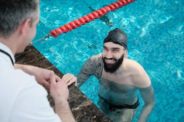 Souriant nageur barbu avec tatouage assis dans la piscine et écoutant l'entraîneur