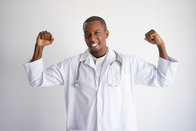 Souriant noir homme médecin pompant les poings et célébrant le succès.