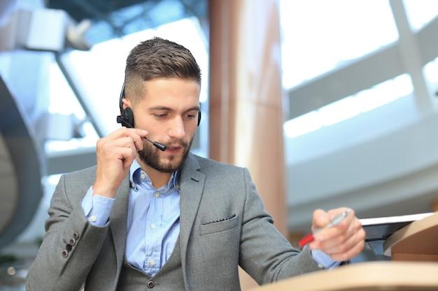 Souriant opérateur de centre d'appels beau jeune homme sympathique.