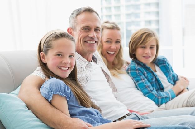 Souriant parents et enfants assis sur un canapé