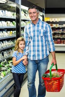 Souriant père et fille au supermarché