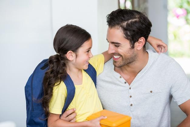 Souriant père et fille avec boîte à lunch