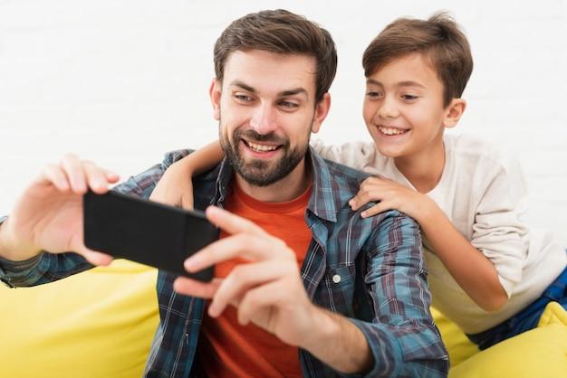 Souriant père et fils prenant des selfies