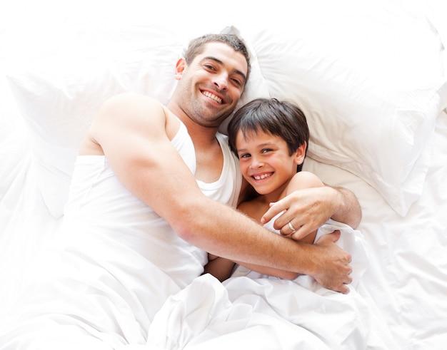 Souriant, père et fils, regarder dans la caméra