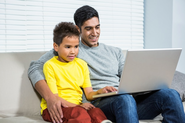 Souriant père et fils utilisant un ordinateur portable sur le canapé