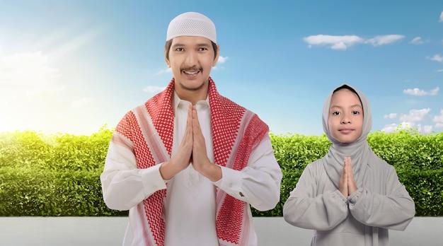Souriant père musulman asiatique et fille priant ensemble