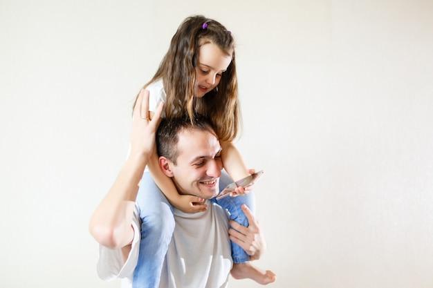 Souriant père portant sur ses épaules sa petite fille isolée sur fond blanc