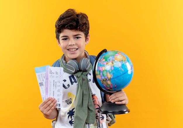 Souriant petit écolier portant sac à dos et écouteurs tenant des billets et globe