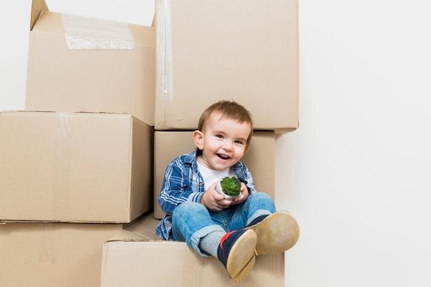 Souriant petit garçon assis sur la boîte en carton en mouvement tenant la plante de cactus