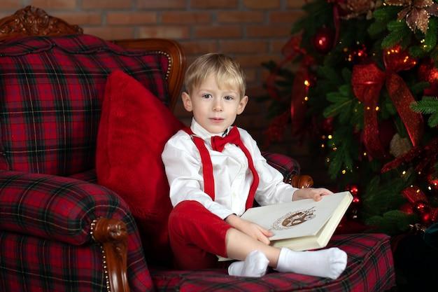 Souriant petit garçon lisant un livre devant l'arbre de noël