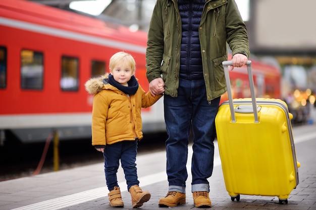 Souriant petit garçon et son père attendant un train express sur le quai de la gare