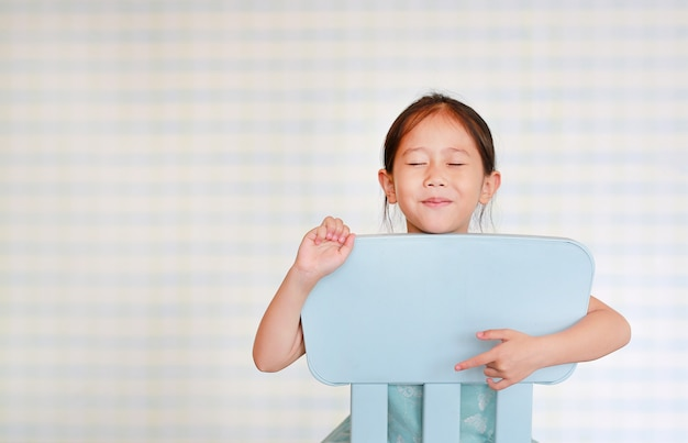 Souriant petite fille asiatique d'âge préscolaire dans une salle de jardin d'enfants pose sur une chaise en plastique