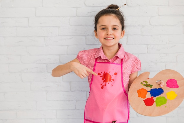 Souriant petite fille debout devant le mur de briques blanches pointant vers la palette colorée dans la main