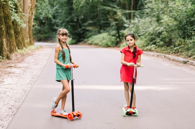 Souriant petites filles debout sur le scooter de poussée sur route